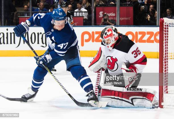 Cory Schneider of the New Jersey Devils makes a save on Leo Komarov of the Toronto Maple Leafs during the first period at the Air Canada Centre on...