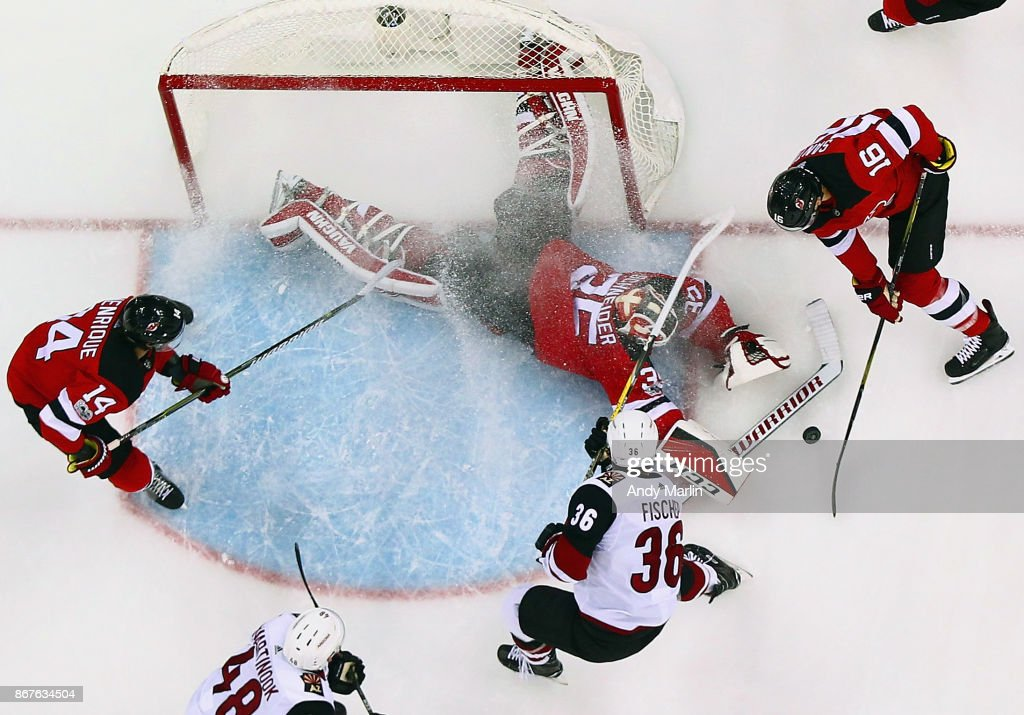 Cory Schneider #35 of the New Jersey Devils makes a stick save laying on the ice during the game against the Arizona Coyotes at Prudential Center on October 28, 2017 in Newark, New Jersey.
