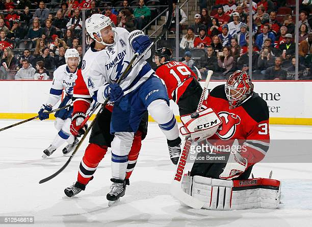 Cory Schneider of the New Jersey Devils makes the first period blocker save as Ryan Callahan of the Tampa Bay Lightning looks for the rebound at the...