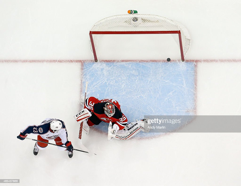 Cory Schneider #35 of the New Jersey Devils playing in his 200th career NHL game cannot stop a goal by Justin Falk #44 (not pictured) of the Columbus Blue Jackets as Brian Gibbons #23 looks on during the game at the Prudential Center on March 6, 2015 in Newark, New Jersey.