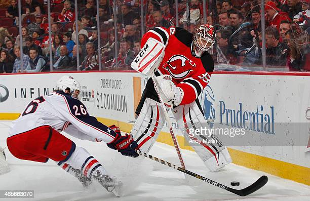 Cory Schneider of the New Jersey Devils playing in his 200th career NHL game plays the puck away from Corey Tropp of the Columbus Blue Jackets during...