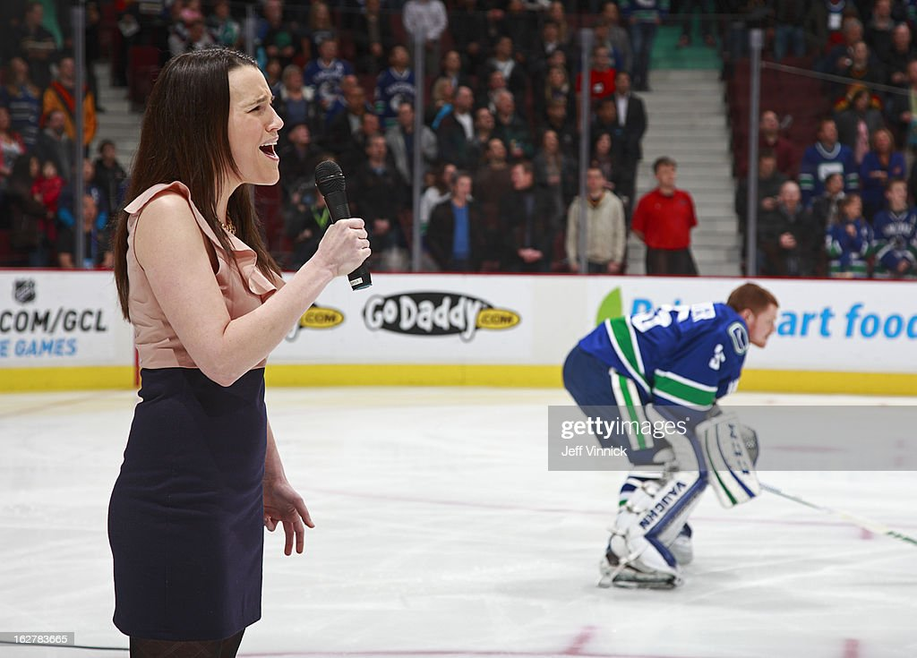 Cory Schneider #35 of the Vancouver Canucks looks on as Sarah Simpson sings the national anthems before their NHL game against the Phoenix Coyotes at Rogers Arena February 26, 2013 in Vancouver, British Columbia, Canada. Phoenix won 4-2.