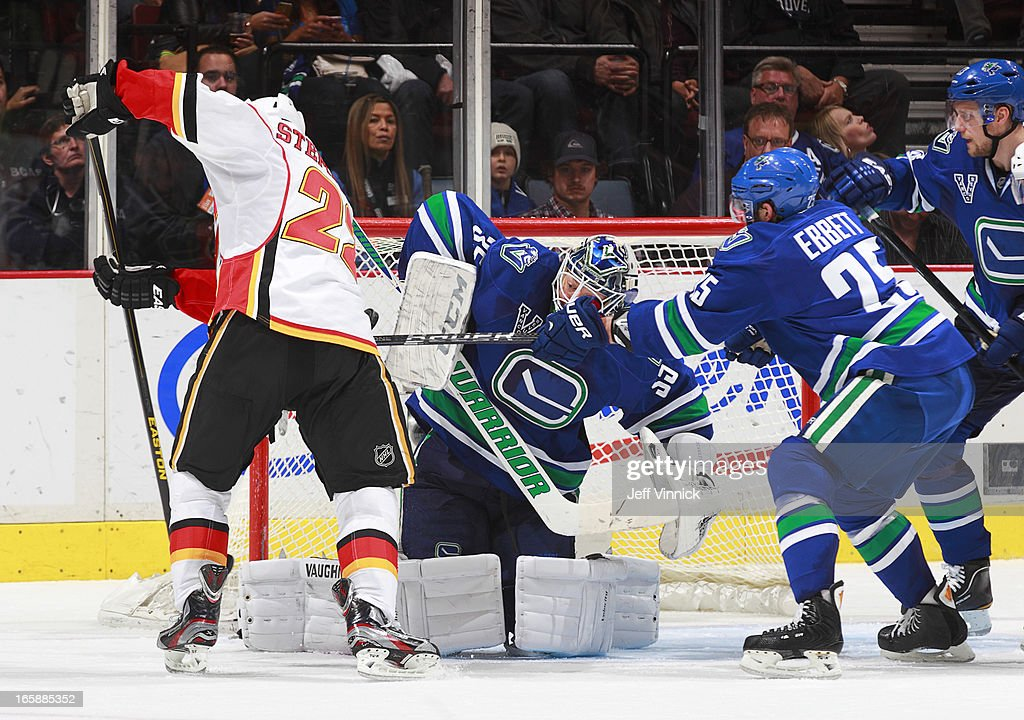 <a gi-track='captionPersonalityLinkClicked' href=/galleries/search?phrase=Cory+Schneider&family=editorial&specificpeople=696908 ng-click='$event.stopPropagation()'>Cory Schneider</a> #35 of the Vancouver Canucks makes a save while <a gi-track='captionPersonalityLinkClicked' href=/galleries/search?phrase=Andrew+Ebbett&family=editorial&specificpeople=4143929 ng-click='$event.stopPropagation()'>Andrew Ebbett</a> #25 freaches in to check <a gi-track='captionPersonalityLinkClicked' href=/galleries/search?phrase=Lee+Stempniak&family=editorial&specificpeople=575240 ng-click='$event.stopPropagation()'>Lee Stempniak</a> #22 of the Calgary Flames during their NHL game against the Vancouver Canucks at Rogers Arena April 6, 2013 in Vancouver, British Columbia, Canada. Vancouver won 5-2