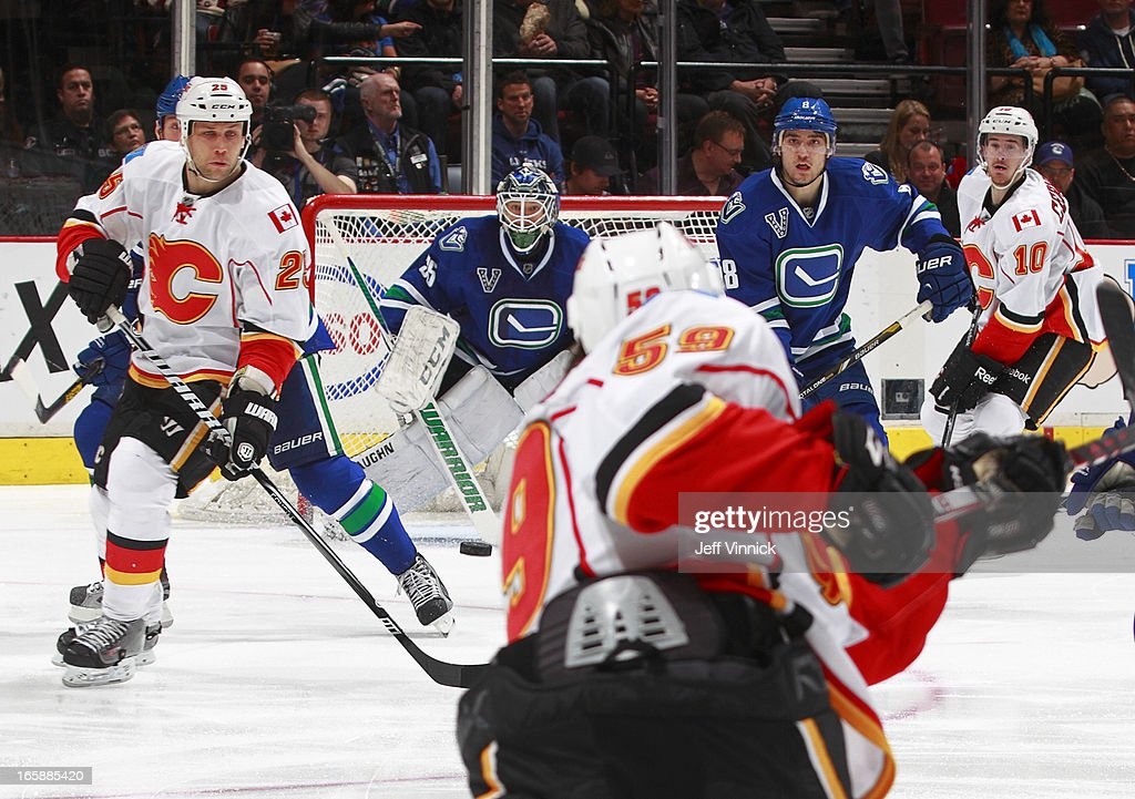 <a gi-track='captionPersonalityLinkClicked' href=/galleries/search?phrase=Cory+Schneider&family=editorial&specificpeople=696908 ng-click='$event.stopPropagation()'>Cory Schneider</a> #35 of the Vancouver Canucks, <a gi-track='captionPersonalityLinkClicked' href=/galleries/search?phrase=Steve+Begin&family=editorial&specificpeople=212983 ng-click='$event.stopPropagation()'>Steve Begin</a> #25 of the Calgary Flames and <a gi-track='captionPersonalityLinkClicked' href=/galleries/search?phrase=Christopher+Tanev&family=editorial&specificpeople=7228624 ng-click='$event.stopPropagation()'>Christopher Tanev</a> #8 of the Canucks watch an oncoming shot from Maxwell Reinhart #59 of the Flames during their NHL game at Rogers Arena April 6, 2013 in Vancouver, British Columbia, Canada. Vancouver won 5-2