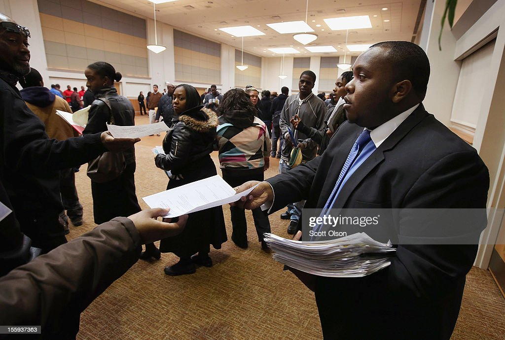 Cory Thames, with the city of Chicago human resources department, collects resumes from Job seekers as they enter a job fair being held at Kennedy-King College and hosted by the city of Chicago on November 9, 2012 in Chicago, Illinois. Thousands of people waited in line beginning at 3AM for the job fair which did not open the doors until 9AM. When the doors opened the line was about a half-mile long.