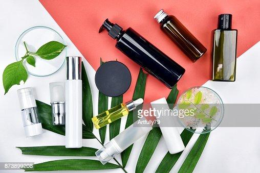Kosmetische Flasche Behälter mit Kräuter-, grünen Blättern, leere Beschriftung für branding Mock-up, natürliche Schönheit Produktkonzept, lag flach auf farbigem Hintergrund. : Stock-Foto