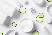 Top view of cosmetic products with slices of cucumber and towels on white background. High angle view of beauty products. Moisturizer and other skincare products with napkin on white background. 'r