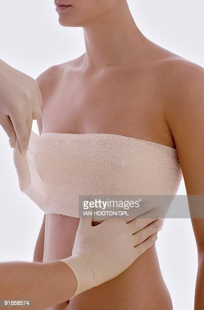 Cosmetic surgeon applying protective bandage round client breasts after surgery