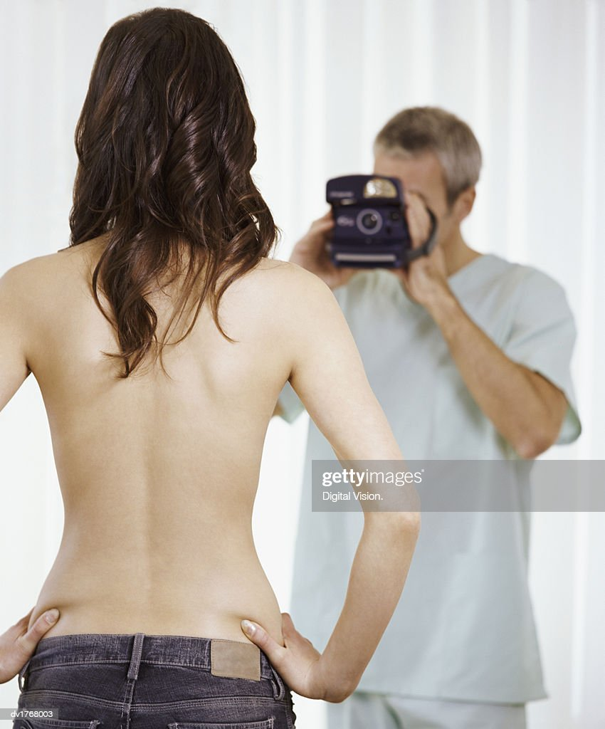 Cosmetic Surgeon Photographing a Topless Patient : Stock Photo