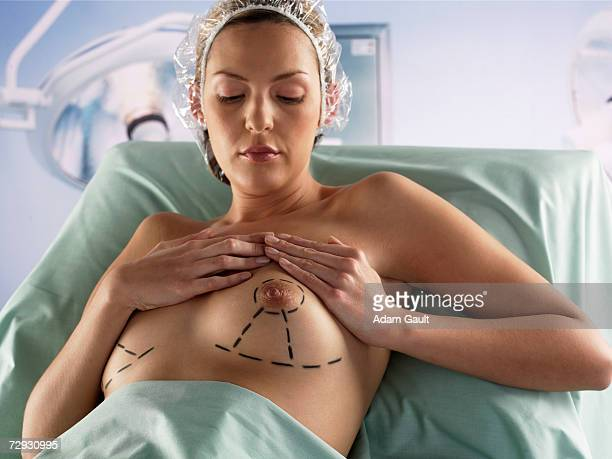 Cosmetic surgery patient, holding breast
