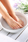 A woman washes the feet in a bowl of water and salt to the foot
