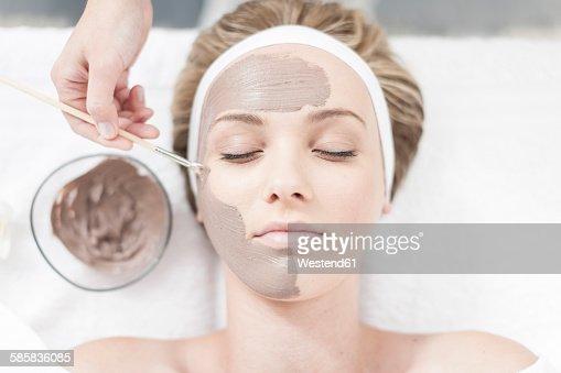 Cosmetician applying beauty mask
