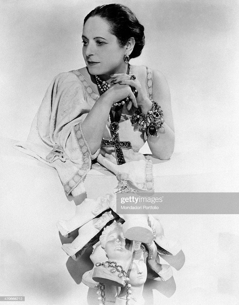 'Cosmetics entrepreneur Helena Rubinstein taken in an elaborate photographic composition leaning on a white base and gazing pensively towards the...