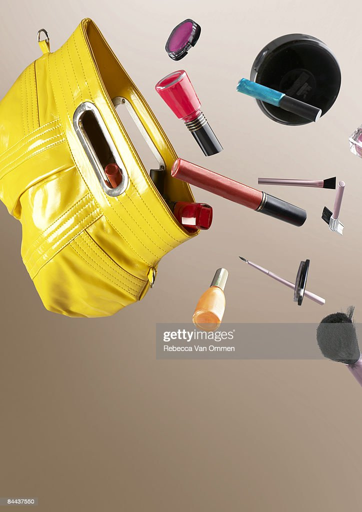 cosmetics falling out of a hand bag : Stock Photo