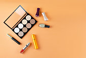 Cosmetics lies on a soft peach background. The contents of women's cosmetic bags. Visagiste
