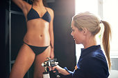 Cosmetologist using aerograph for spray tan apply to young woman leg in beauty salon.