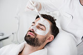 Relaxed bearded young man being in spa salon and professional cosmetologist putting white clay mask on his face with a brush