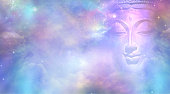 Semi transparent Buddha face with closed eyes amongst the celestial heavens providing a beautiful  pink and blue sky background