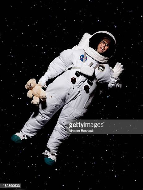 Cosmonaut holding a teddy bear in space