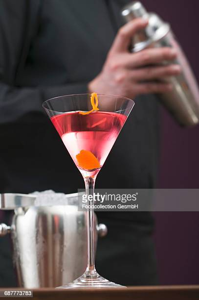 Cosmopolitan in glass, bartender with cocktail shaker