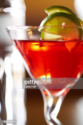 cosmopolitan vodka drink in glass with limes on ta : Stock Photo