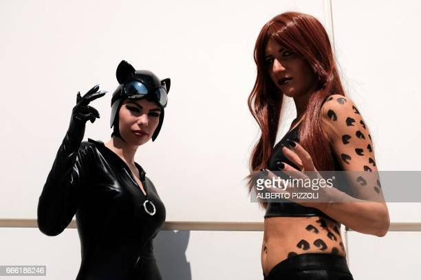 Cosplay enthusiasts dressedup as catwoman pose during the Romics event a comic book and gaming convention in Rome on April 8 2017 Romics is the...