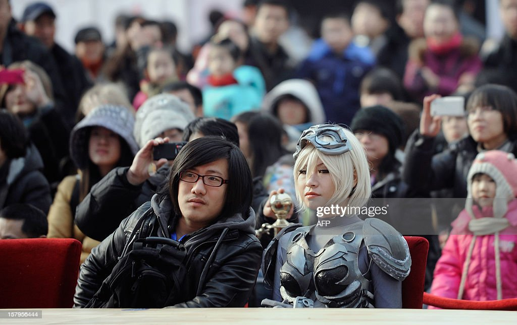 A 'cosplay' fan (R) attends an event at the International Anime Fair in Beijing on December 8, 2012. The fair is being held at the Beijing Crab Island International Convention and Exhibition Centre from December 1 to 9.