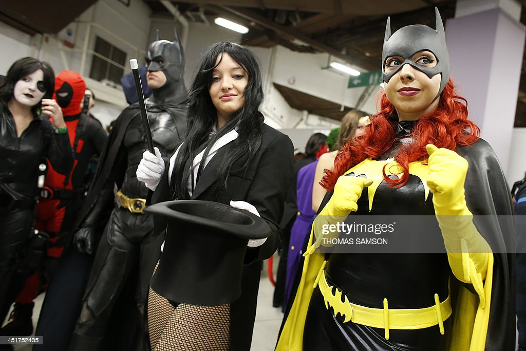 A cosplay fan dressed as batgirl (R) poses as she takes part in a contest with other fans on November 24, 2013 during the 'Paris Comics Expo' at the Espace Champerret in Paris. Organised by Pixidol association, this contest of cosplay (short for 'costume play') marks the 50th anniversary of Marvel Comics' X-Men and The Avengers. AFP PHOTO / THOMAS SAMSON