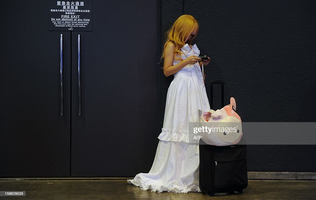 A cosplay fan looks at her mobile phone while attending the Asia Game Show (AGS) in Hong Kong on December 22, 2012. The AGS is highlighting products from the electronic gaming industry and runs from December 21 to 24. AFP PHOTO / Dale de la Rey
