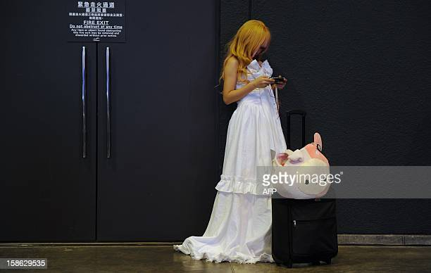 A cosplay fan looks at her mobile phone while attending the Asia Game Show in Hong Kong on December 22 2012 The AGS is highlighting products from the...