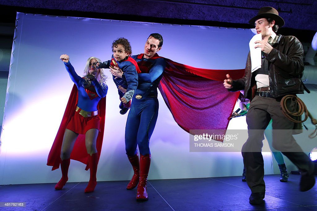 Cosplay fans dressed as Supergirl and Superman pose with a child as they take part in a contest on November 24, 2013 during the 'Paris Comics Expo' at the Espace Champerret in Paris. Organised by Pixidol association, this contest of cosplay (short for 'costume play') marks the 50th anniversary of Marvel Comics' X-Men and The Avengers.