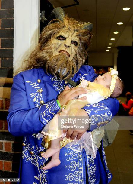 A cosplayer dressed as Disney's Beast with baby daughter dressed as Belle of Beauty and the Beast attend MCM Comic Con at Manchester Central on July...