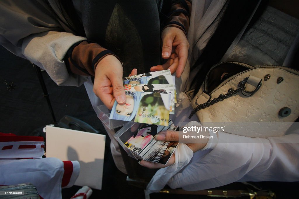 Cosplayers exchange their name cards during the final day of AniManGaki on August 25, 2013 in Kuala Lumpur, Malaysia. AniManGaki, which is now into its fifth year, attracts fans of Anime, Manga and Cosplay from across Asia who gather together to celebrate the genre.