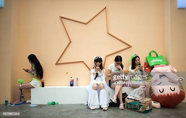 Cosplayers rest during the China Joy fair in Shanghai on July 31 2014 The gamer fair China Joy opens its doors from July 31 to August 3 2014 AFP...