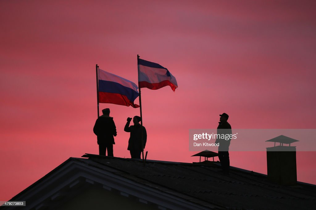 Cossack men install a Russian flag and a Crimean flag on the roof of the City Hall building on March 17, 2014 in Bakhchysarai, Ukraine. People in Crimea overwhelmingly voted to secede from Ukraine during a referendum vote on March 16 and the Crimean Parliament has declared Independence and formally asked Russia to annex them.
