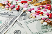 Heap of pharmaceutical drug and medicine pills scattered on dollar cash money, cost of medicinal product and treatment concept