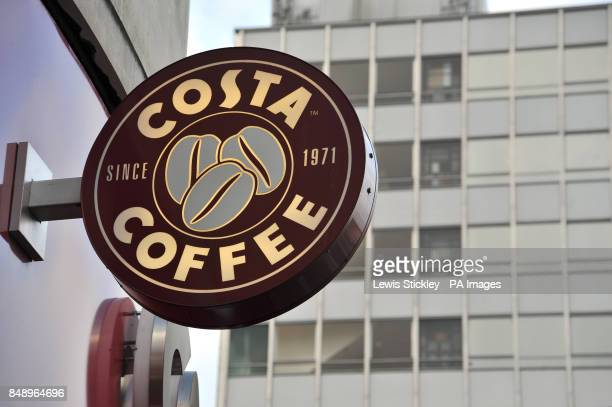 A Costa Coffee sign is seen in front of office buildings in the distance