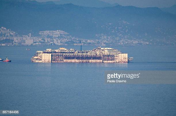 Costa Concordia ship being towed after first scrapping works at Genoa port Italy