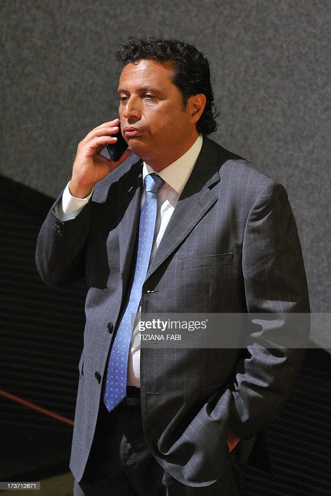 Costa Concordia's captain Francesco Schettino reacts as he speaks on his mobile phone before taking place for his trial on July 17, 2013 in a local theatre in Grosseto. Captain Francesco Schettino, dubbed Italy's 'most hated man' by tabloids over the spectacular crash of his cruise ship in 2012 with the loss of 32 lives, went on trial on Tuesday charged with manslaughter.