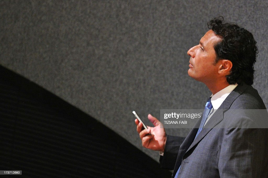 Costa Concordia's captain Francesco Schettino reacts as he speaks on his mobile phone before taking place for his trial on July 17, 2013 in a local theatre in Grosseto. Captain Francesco Schettino, dubbed Italy's 'most hated man' by tabloids over the spectacular crash of his cruise ship in 2012 with the loss of 32 lives, went on trial on Tuesday charged with manslaughter. AFP PHOTO / TIZIANA FABI