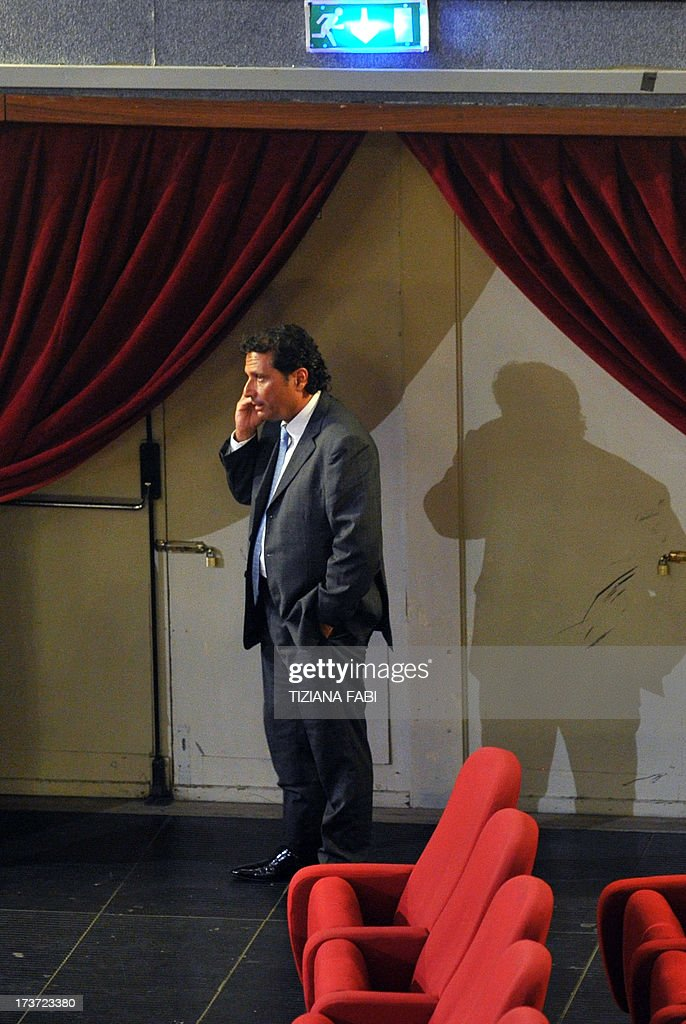 Costa Concordia's captain Francesco Schettino speaks on his mobile phone during a break of his trial on July 17, 2013 in a local theatre in Grosseto. Captain Francesco Schettino, dubbed Italy's 'most hated man' by tabloids over the spectacular crash of his cruise ship in 2012 with the loss of 32 lives, went on trial on Tuesday charged with manslaughter. AFP PHOTO / TIZIANA FABI