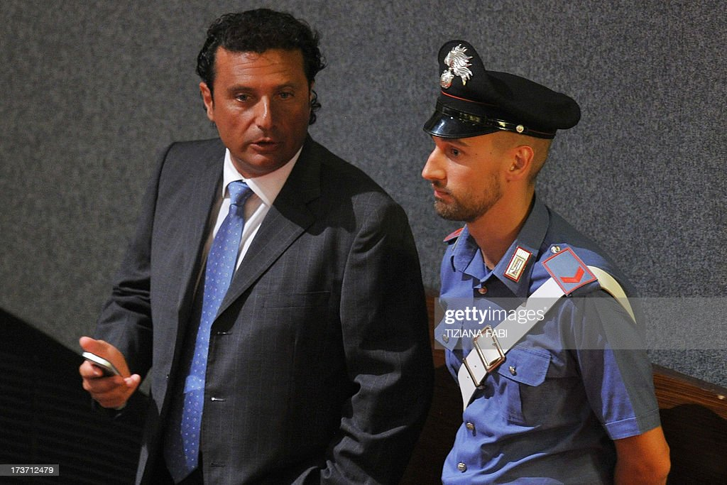 Costa Concordia's captain Francesco Schettino (L) speaks with a policeman as he takes place for his trial on July 17, 2013 in a local theatre in Grosseto. Captain Francesco Schettino, dubbed Italy's 'most hated man' by tabloids over the spectacular crash of his cruise ship in 2012 with the loss of 32 lives, went on trial on Tuesday charged with manslaughter.