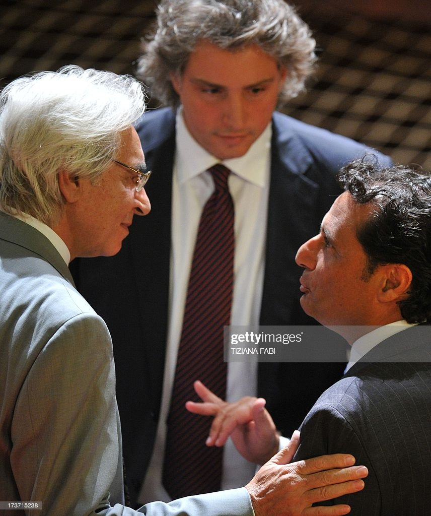 Costa Concordia's captain Francesco Schettino (R) speaks with his lawyers Domenico Pepe (L) and Francesco Pepe (C) before taking place for his trial on July 17, 2013 in a local theatre in Grosseto. Captain Francesco Schettino, dubbed Italy's 'most hated man' by tabloids over the spectacular crash of his cruise ship in 2012 with the loss of 32 lives, went on trial on Tuesday charged with manslaughter. AFP PHOTO / TIZIANA FABI