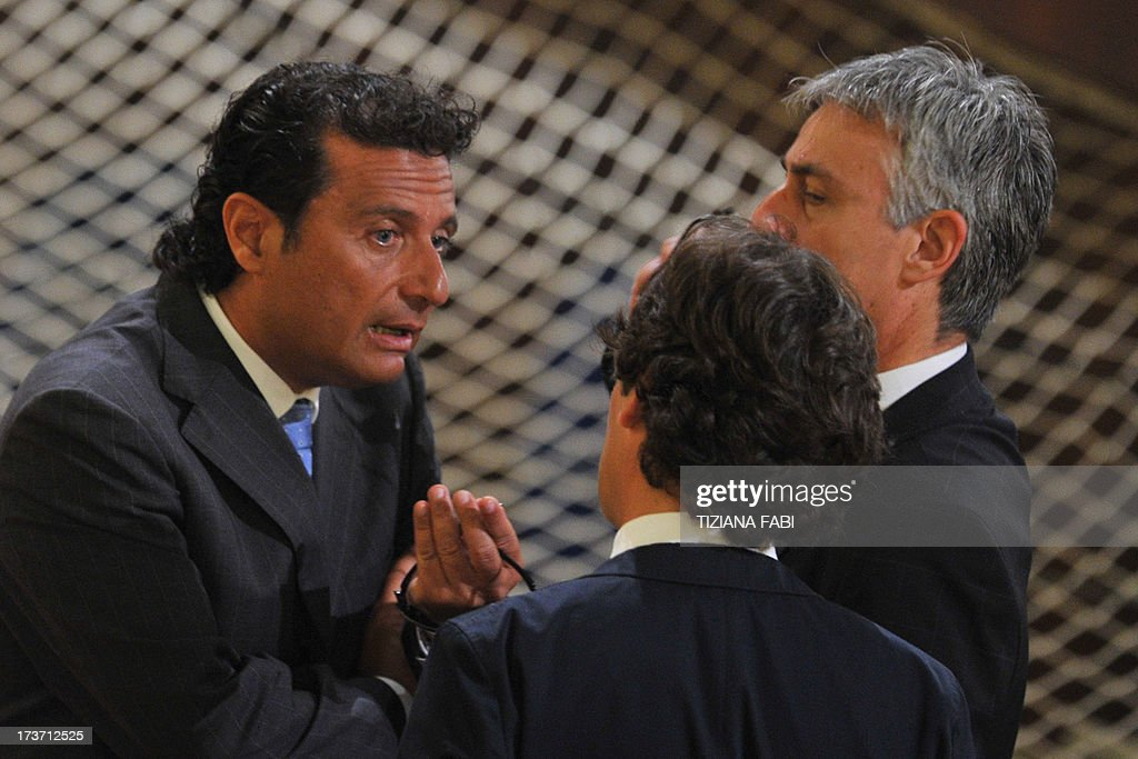 Costa Concordia's captain Francesco Schettino (L) speaks with officials before taking place for his trial on July 17, 2013 in a local theatre in Grosseto. Captain Francesco Schettino, dubbed Italy's 'most hated man' by tabloids over the spectacular crash of his cruise ship in 2012 with the loss of 32 lives, went on trial on Tuesday charged with manslaughter.