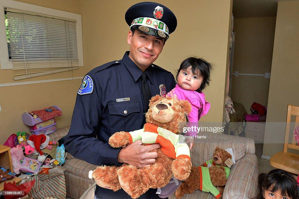 Costa Mesa Fire Department Engineer Eliasar Maldonado gives a teddy bear to an underpriviledged family for the 12th Annual Costa Mesa Fire Department Santa Letters on December 22, 2012 in Costa Mesa, California.