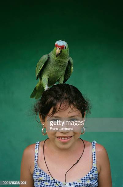 Costa Rica, Fortuna, girl with parrot perched on head, smiling