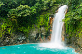 This is a horizontal, royalty free stock photograph of scenic Costa Rica, a Central American travel destination. The Rio Celeste waterfall is a natural landmark for eco tourists visiting Tenorio Natio
