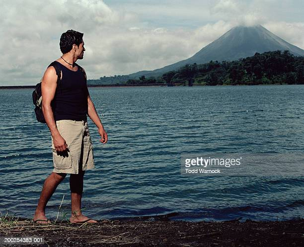 Costa Rica, young man standing in lake, looking at Arenal Volcano