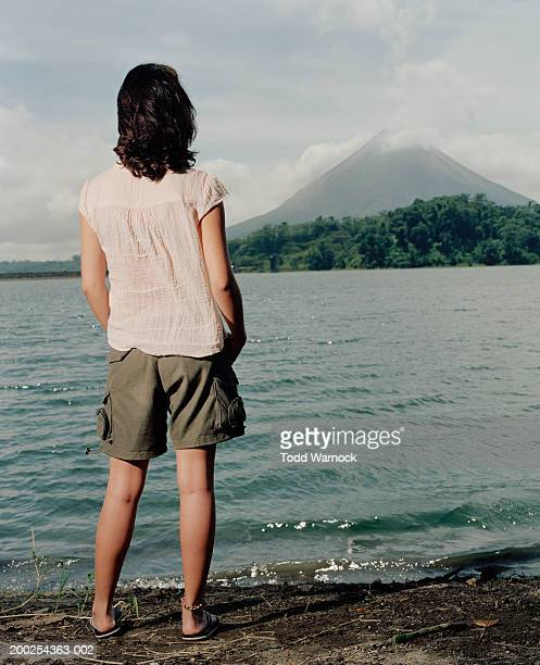 Costa Rica, young woman looking at Arenal Volcano, rear view