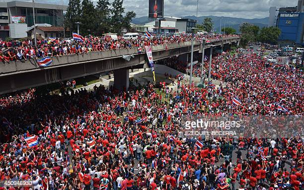 Costa Rican fans celebrate in San Jose on June 20 2014 after defeating Italy in a Brazil 2014 FIFA World Cup football match and reaching the second...